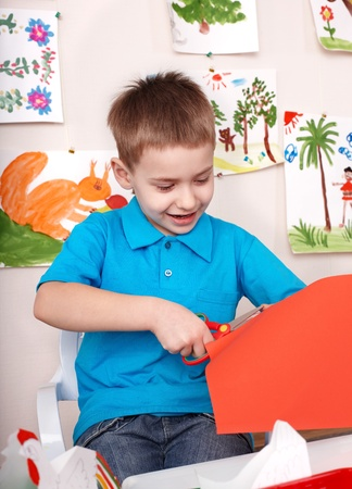 knippen: Ernstige kind snijden papier door schaar. Stockfoto