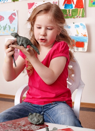 sculp: Little girl playing with clay. Stock Photo