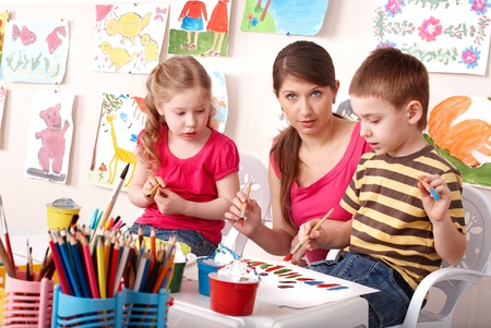 Little girl and boy  painting with teacher in school. photo