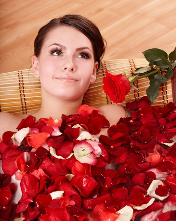 Beautiful young woman in rose petal swim water. Beauty spa. photo