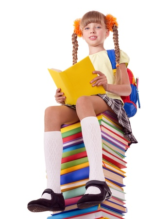 Schoolgirl sitting on pile of books. Isolated. photo