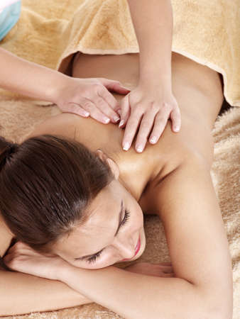 massage table: Young woman having classical massage in beauty spa. Series.