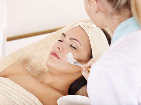 Beautician applying  facial mask by young woman. Stock Photo - 9284265