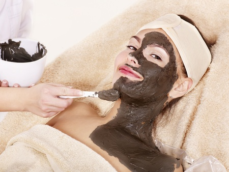beauty parlour: Beautiful girl having clay body mask apply by beautician.