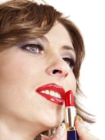 Beautiful woman applying lipstick. Isolated. photo