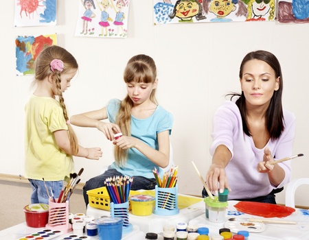 Children painting in preschool. Teacher help by little girl. photo