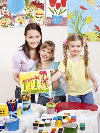 maestra preescolar: Ni�o pintura en preescolar. Profesor ayuda por la ni�a. Foto de archivo