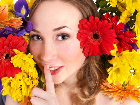 Beauty young woman in flowers making silence gesture. Stock Photo