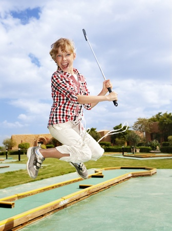 Child playing golf in park. Outdoor.