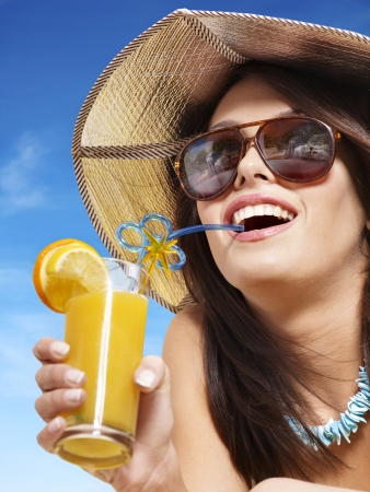 summer clothing: Girl in bikini drink juice through a straw. Stock Photo