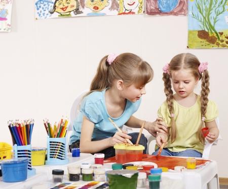 Happy children painting in preschool.  Stock Photo - 9385640