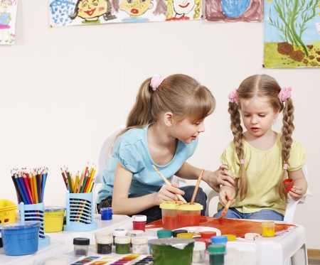play of color: Happy children painting in preschool.