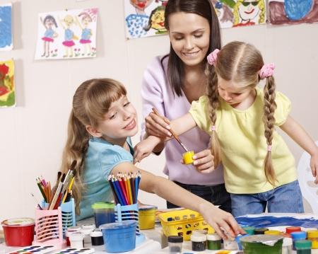 Niño pintura en preescolar. Profesor ayuda por la niña.