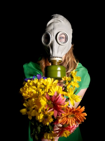 Young woman  in gas mask and flowers .Toxic Environment photo