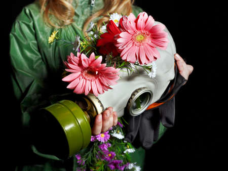 Female hands holding  gas mask with flowers . Stock Photo - 9380589