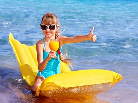 little girl swimsuit: Little girl swimming on inflatable beach mattress. Stock Photo