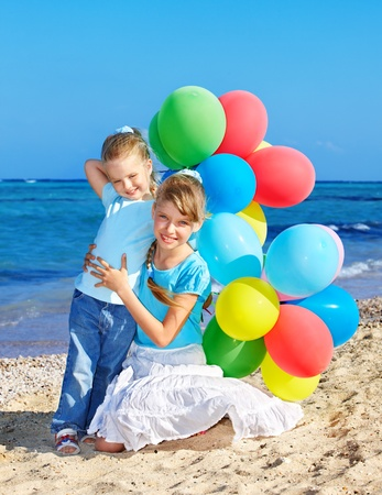 birthday party kids: little girl playing with balloons at the beach. Stock Photo