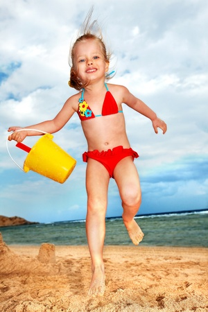 water bucket: Little girl  playing on  beach.