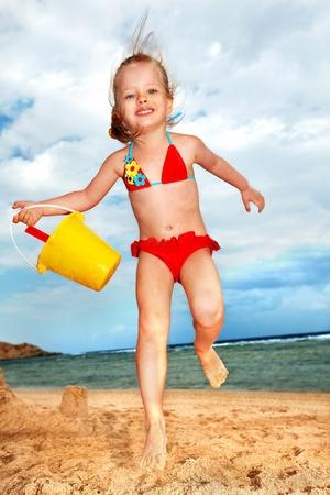 seau d eau: Petite fille jouant sur la plage.