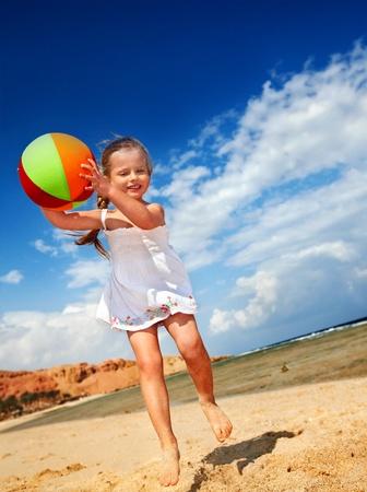 piedi nudi di bambine: Bambina giocando sulla spiaggia con la palla. Archivio Fotografico