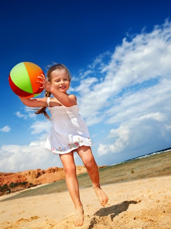 little girl smiling: Little girl  playing on  beach with ball.