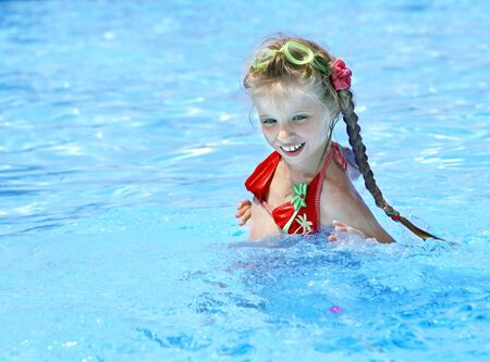 Little girl swim in swimming pool. photo