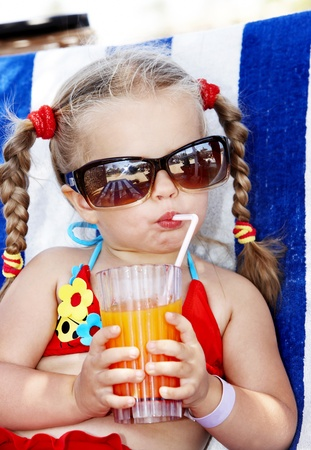 summer drink: Little girl in glasses and red bikini drink orange juice. Stock Photo