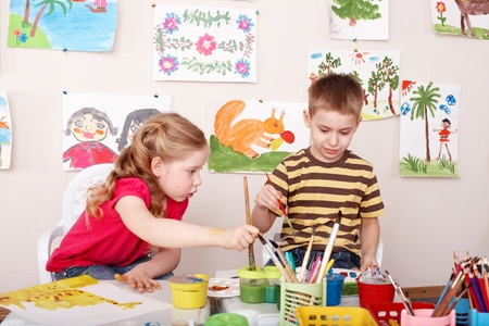 children painting: Children painting in play room. Child care. Stock Photo
