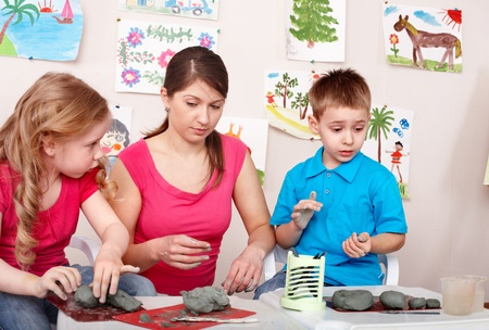 child care: Children mould with teacher from clay. Child development. Stock Photo