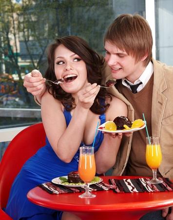 Loving couple eating cake in restaurant. photo