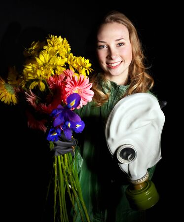 Young woman holding flowers and gas mask . photo