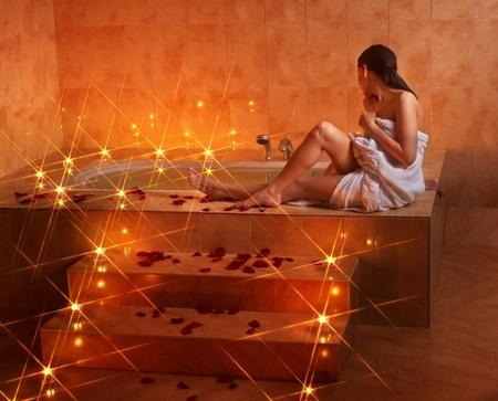 bath tub: Woman sitting on edge of bath tub.