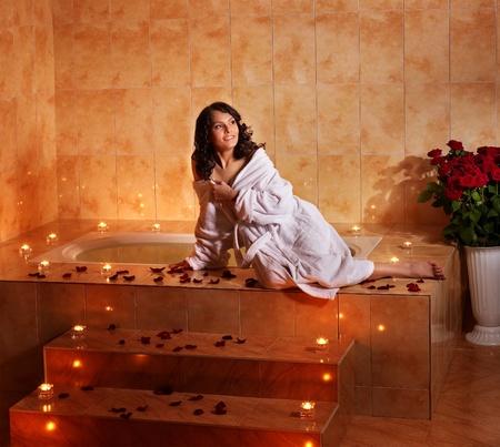 swimming candles: Woman sitting on edge of bath tub.