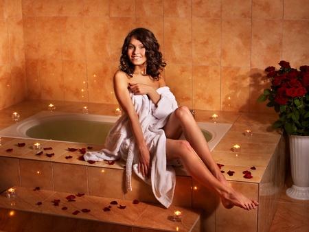 Woman sitting on edge of bath tub. photo
