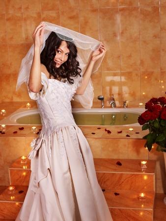 Woman in  wedding dress relaxing in bath tube. photo