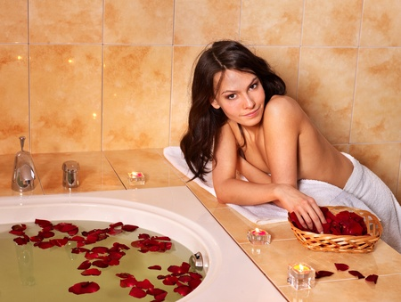 Woman sitting on edge of bath tub. photo