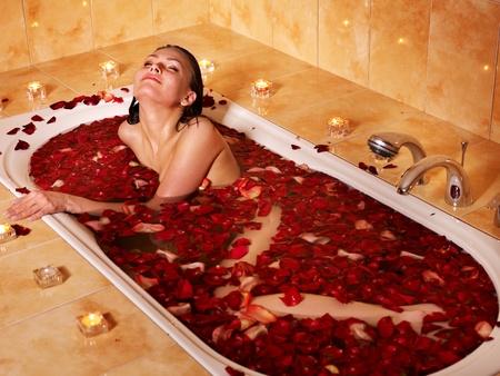 ba�arse: Mujer relajante en ba�o con p�talos de rosas.