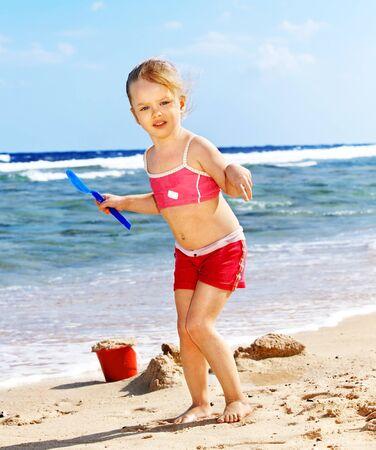 Little girl  playing on  beach. photo