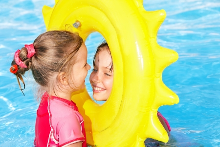 one piece swimsuit: Children playing inflatable ring in swimming pool.