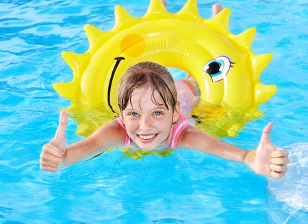 Children sitting on inflatable ring in swimming pool. Stock Photo - 9620123