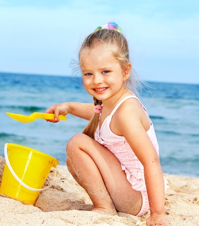 Little girl  playing on  beach. Stock Photo - 9620127