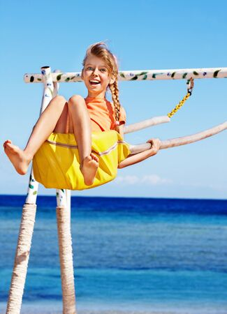 Happy little girl swinging on  swing . Stock Photo
