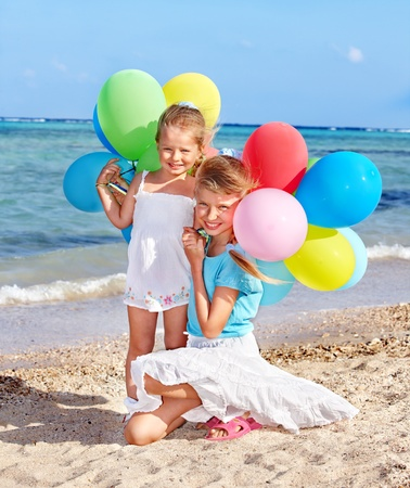 kids playing beach: little girl playing with balloons at the beach. Stock Photo