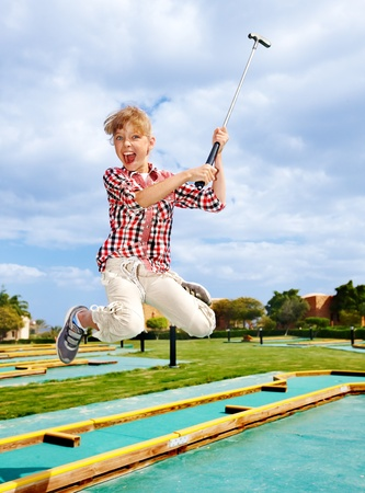 Children playing golf in park. Outdoor. photo