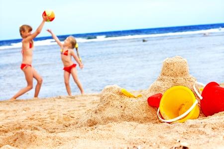 chateau de sable: Petite fille jouant sur la plage avec ballon.