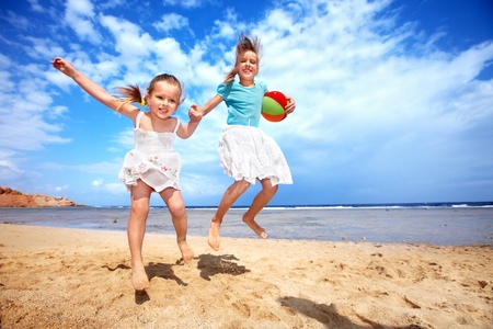 Little girl  playing on  beach with ball.