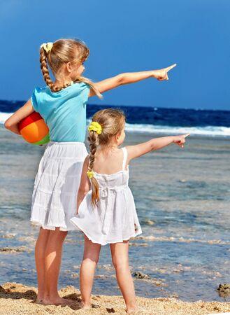 Mała dziewczynka gra na plaży z piłką.