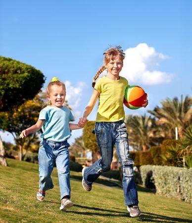 Children running with ball in park. Outdoor. photo