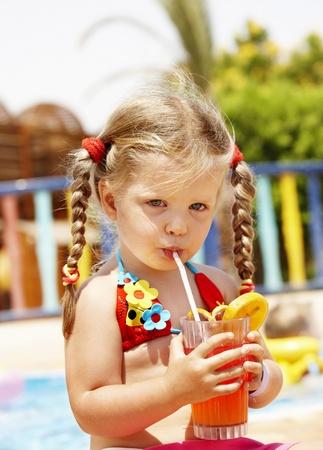 Child girl in glasses and red bikini drink orange juice. photo