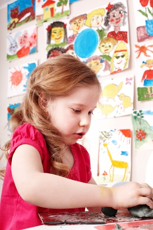 Little girl playing with clay in play room. photo